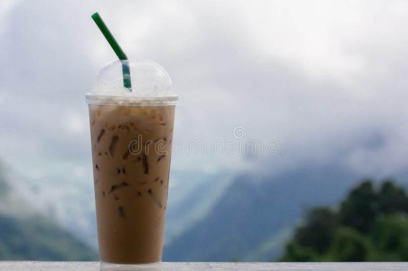 Iced coffee espresso, cappuccino, latte in plastic cup take away with green straw on wooden table with blurry hill background stock images