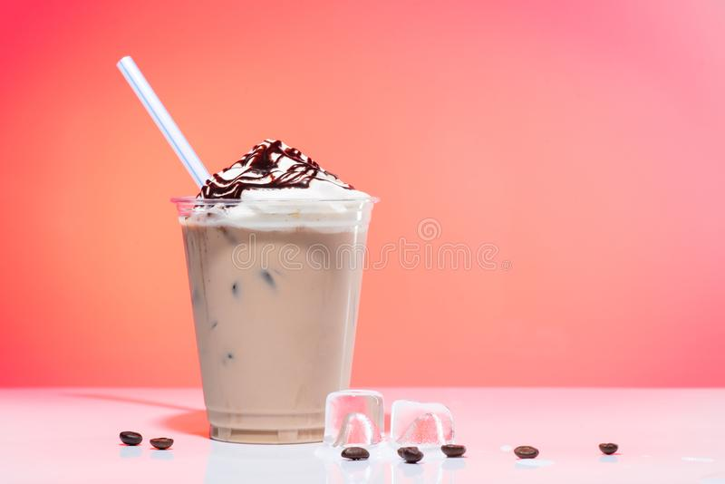 Iced coffee with ice-cream. And drinking straw in glass cup on pink background with copy space for text stock photography