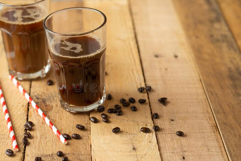 Iced iced coffee in large transparent glasses, poured over milk, with coffee beans on a wooden background, summer cooling drink, royalty free stock photos