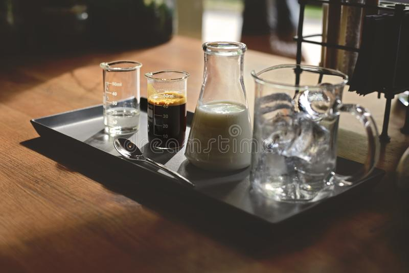 iced coffee latte, ice cubes espresso milk and sweet syrup served in various test tubes on wooden table in morning cafe royalty free stock photo