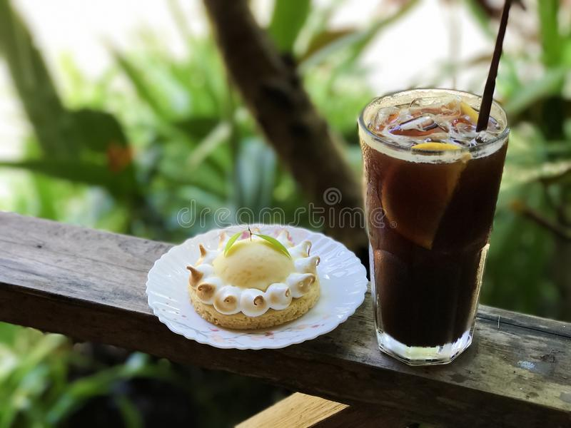 Iced coffee with lemon juice and lemon tart. On the wooden table,blurred background and back light royalty free stock photos