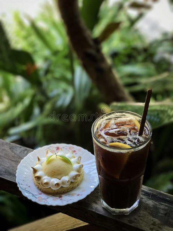 Iced coffee with lemon juice and lemon tart. On the wooden table,blurred background and back light royalty free stock image