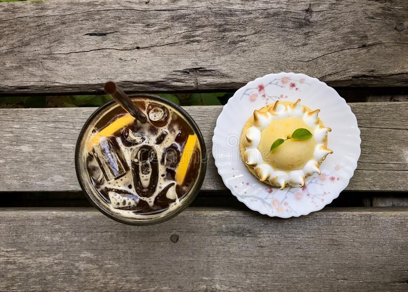 Iced coffee with lemon juice and lemon tart. On the wooden table,top view stock photo