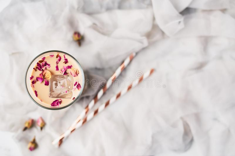 Iced coffee with rose and cardamom in a tall glass stock photography