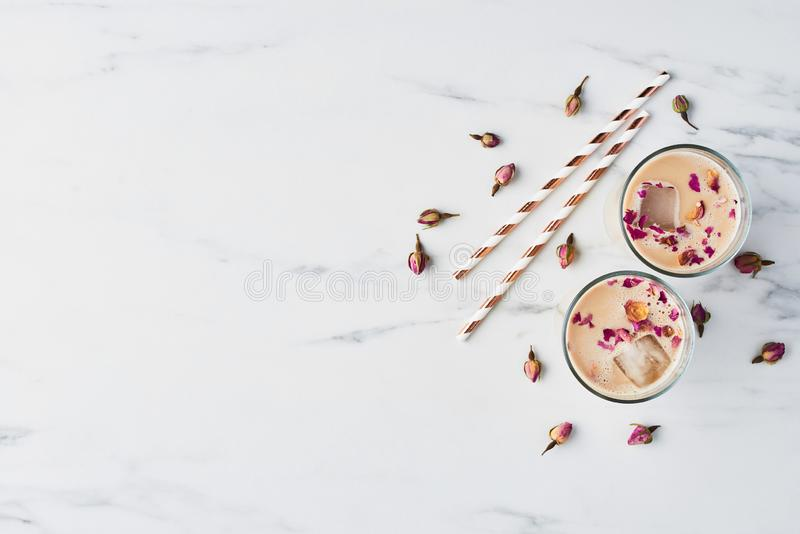 Iced coffee with rose and cardamom in a tall glass stock image