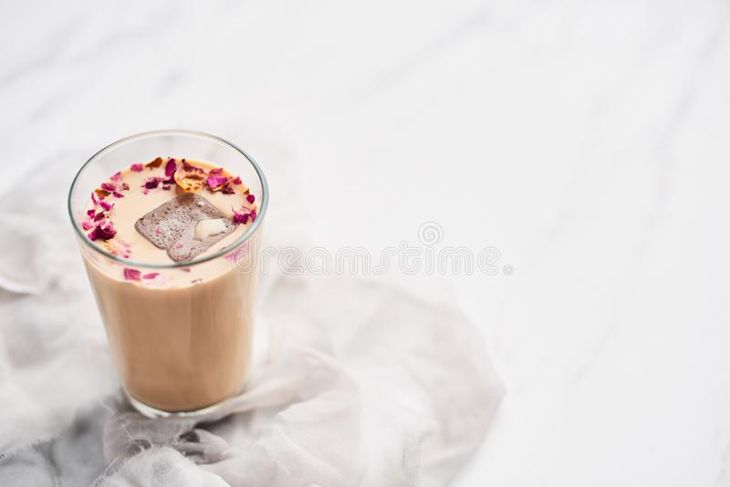 Iced coffee with rose and cardamom in a tall glass royalty free stock photo