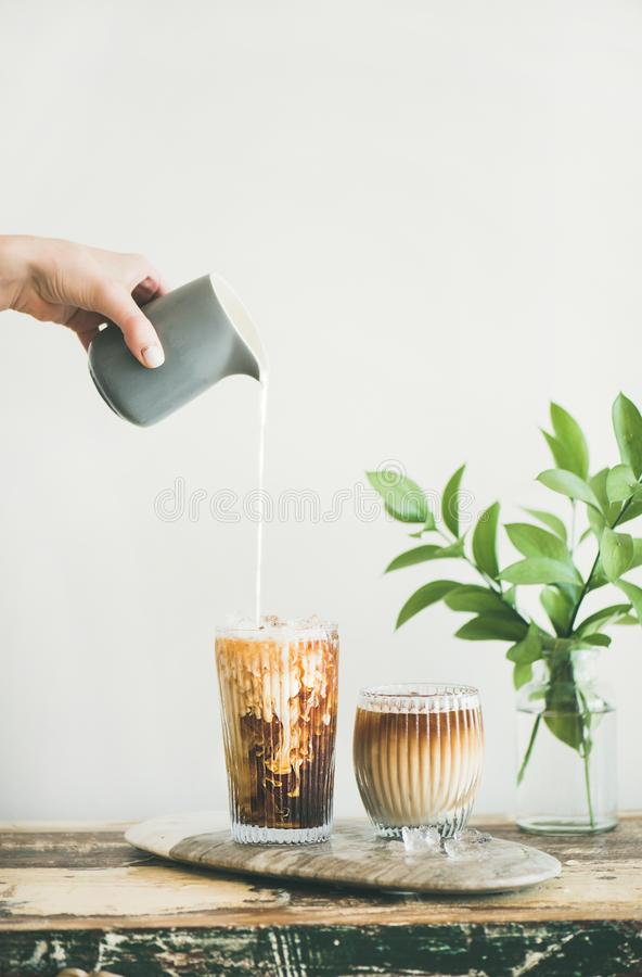 Iced coffee in a tall glass with cream poured over royalty free stock photo
