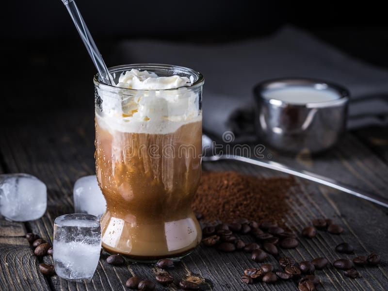 Iced coffee in a tall glass with cream poured over. royalty free stock photos