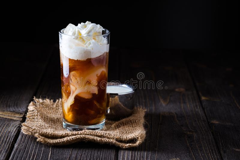Iced coffee in a tall glass with cream poured over. royalty free stock photography