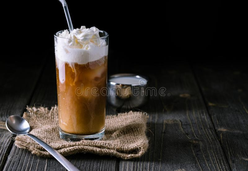 Iced coffee in a tall glass with cream poured over. stock photos