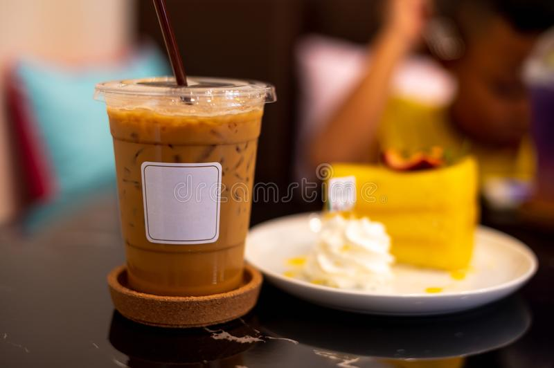 Iced coffee with white label and orange cake. On dark background royalty free stock images