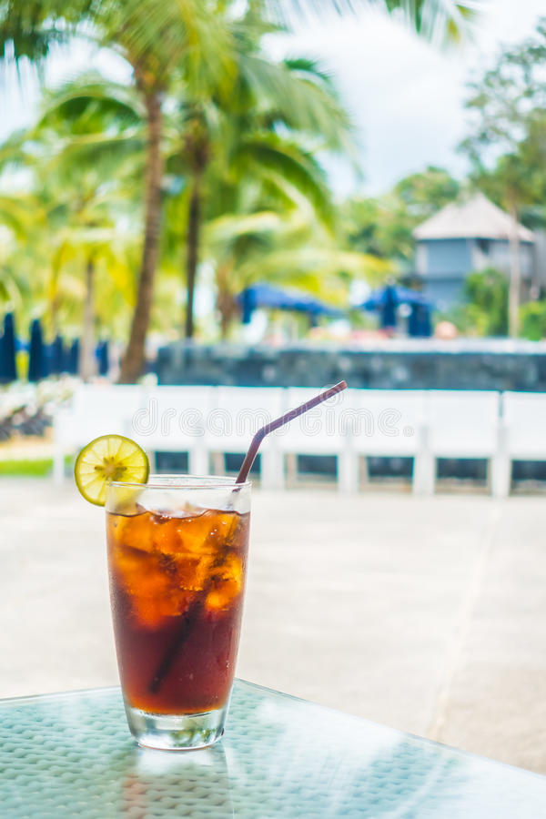 Iced cola glass. With pool view background royalty free stock image