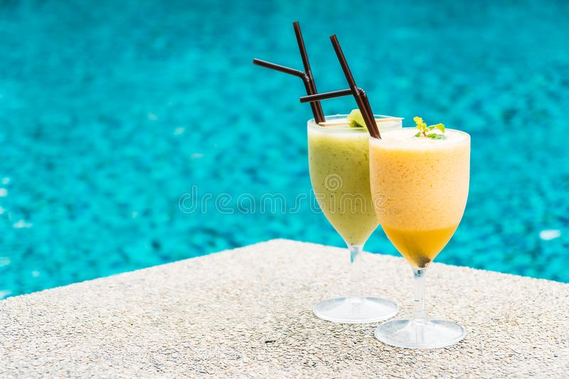 Smoothies with pool background. Iced fruit smoothies with pool background royalty free stock images