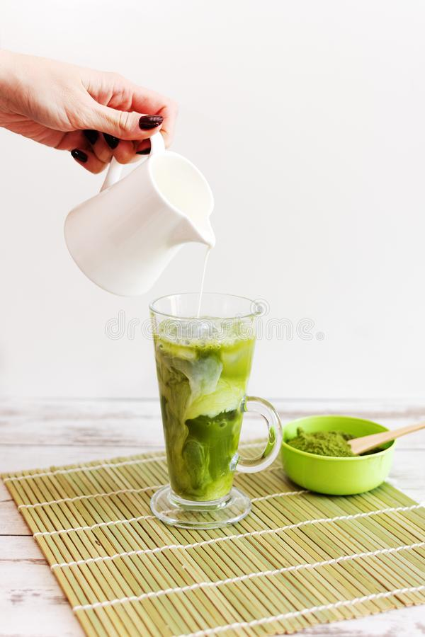 Iced matcha latte drink in tumbler glass with coconut milk pouring from pitcher by hand, copy space stock photos