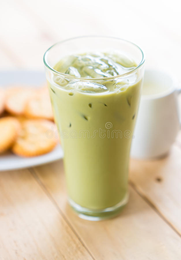 Iced matcha latte. On wood background royalty free stock image