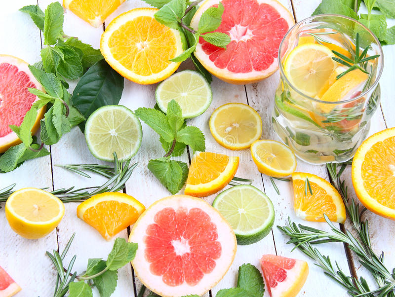 Iced mint tea with lemon. Lime and orange and ice cubes on a rustic background royalty free stock image
