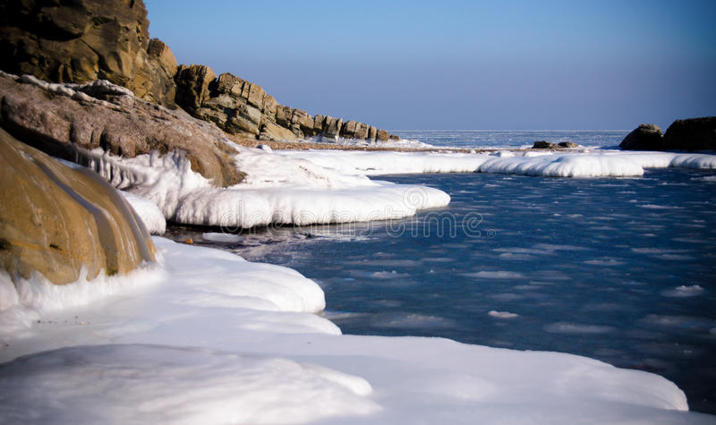 Iced mountains on the seashore in winter stock photography