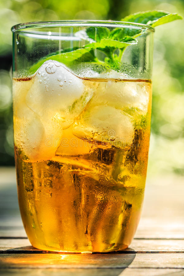 Iced tea. Glass of iced tea with ice-cubes and mint leaves, close-up stock image