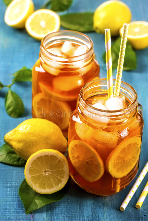 Iced tea with lemon. In glass jars stock photography