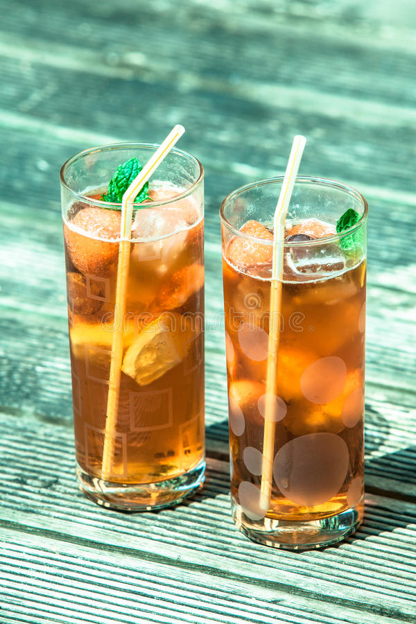 Iced tea with lemon and mint. On wooden table, outdoors royalty free stock images