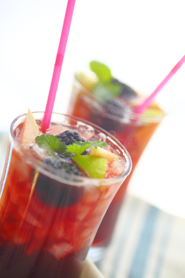 Iced wine drinks with fruit and mint. Closeup view of chilled wine cocktails with fresh apple and blackberries with mint royalty free stock photo