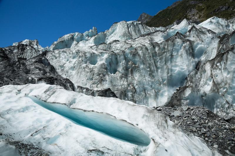 Small crevasse below seracs of an icefall on the Fox Glacier in stock photography
