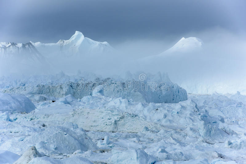 Disko Bay, Icefjord Ilulissat coming out of mist, Greenland. Beautiful icebergs coming out the fog in unique icefjord of Qeqertarsuup tunua - Ilulissat royalty free stock photo