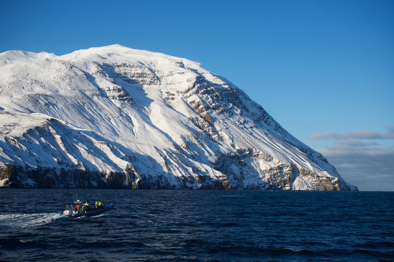 Iceland cliffs view from the sea in winter including speed boat. Ocean stock photography
