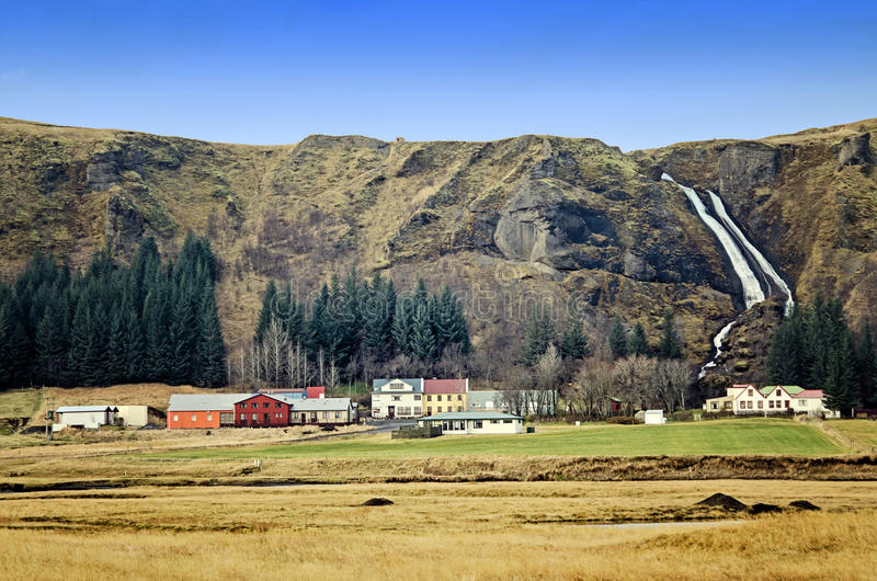 Iceland houses. Colorful houses below mountain and waterfall in Southern Iceland royalty free stock photography