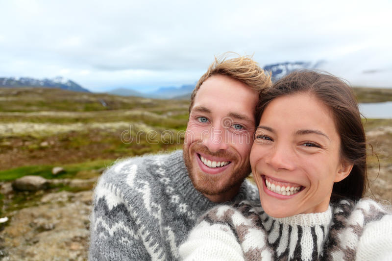 Iceland couple selfie wearing Icelandic sweaters. In beautiful nature landscape on Iceland. Woman and men model in typical Icelandic sweater. Multiracial couple royalty free stock photos