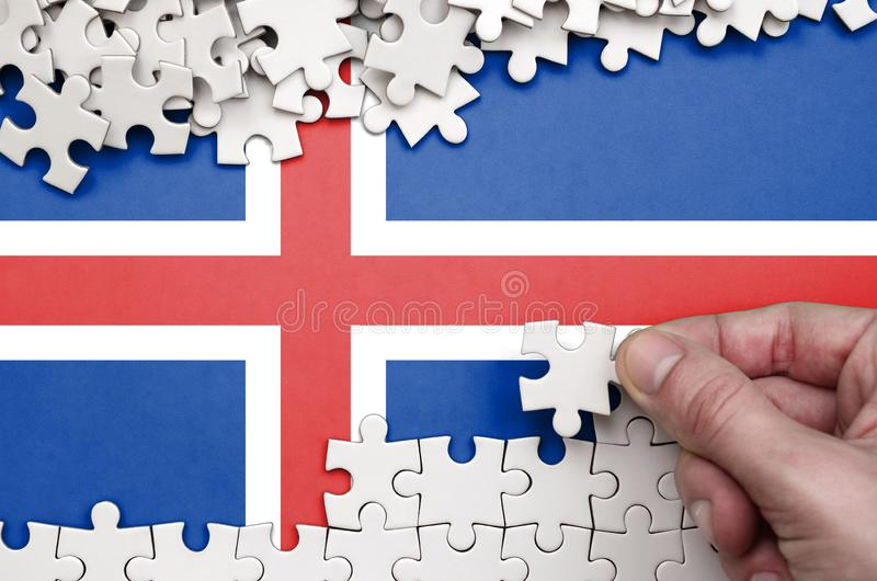 Iceland flag is depicted on a table on which the human hand folds a puzzle of white color stock photo