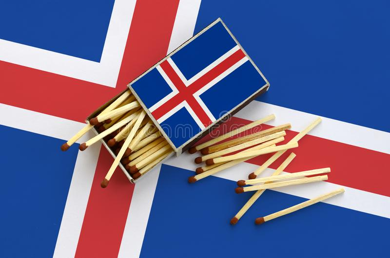 Iceland flag is shown on an open matchbox, from which several matches fall and lies on a large flag.  stock photography