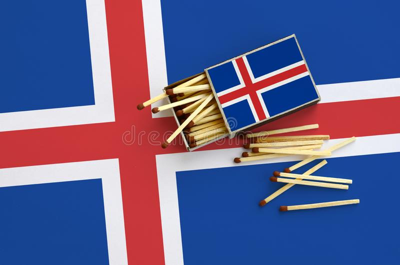 Iceland flag is shown on an open matchbox, from which several matches fall and lies on a large flag.  royalty free stock photos