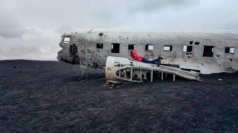 Iceland - Girl lying on a crashed plane on a black sand beach stock photo