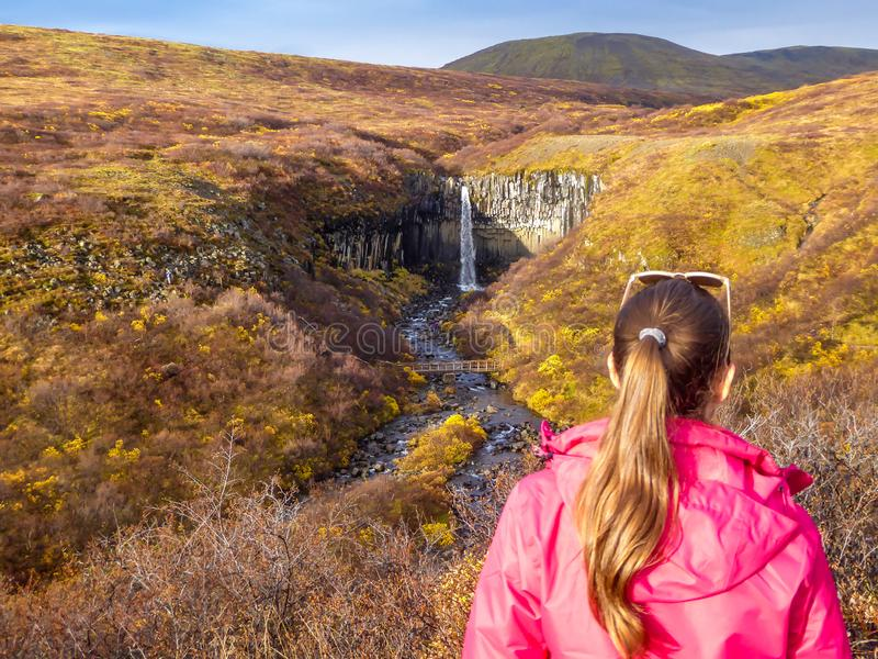 Iceland - A girl standing backwords and admiring a waterfall in front of her royalty free stock images