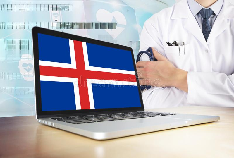 Iceland healthcare system in tech theme. Icelander flag on computer screen. Doctor standing with stethoscope in hospital. Cryptocurrency and Blockchain concept stock photos