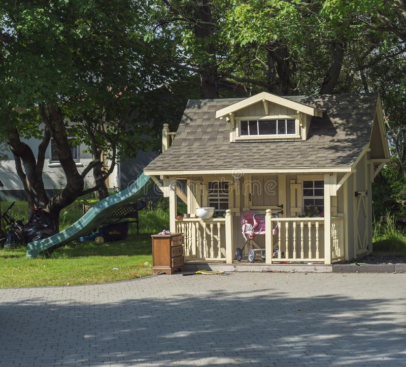 Iceland, Hveragerdi, August 5, 2019: Big cute wooden children house on garden with slide for the children`s games, pink pram and stock photos