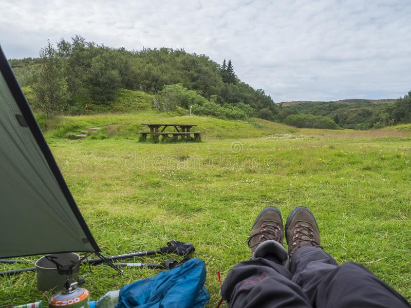 ICELAND, LANDMANNALAUGAR, August 2, 2019: Hikers legs in hiking boots at green tent in camping site in Thorsmork with stock images