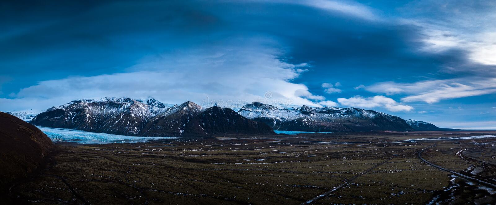 Iceland landscape. Panoramic view of the Iceland landscape with a snowy mountain range in the distance under a dark clouds sky royalty free stock photo