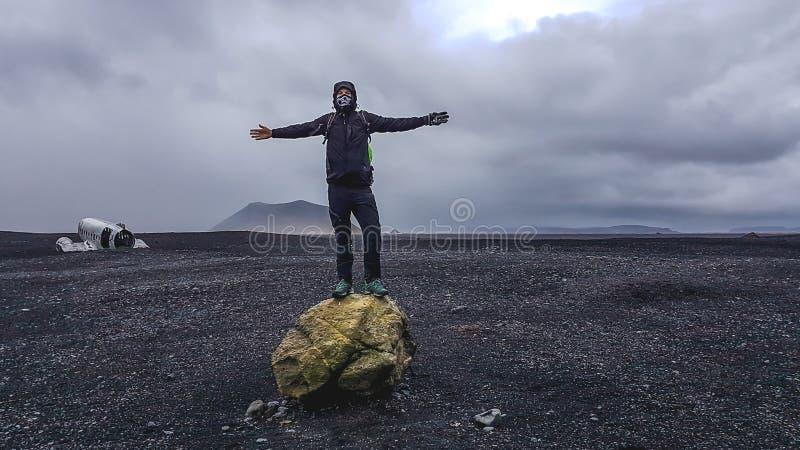 Iceland - m?ody cz?owiek pozycja na du?ej skale z samolotu wrakiem w plecy obraz royalty free