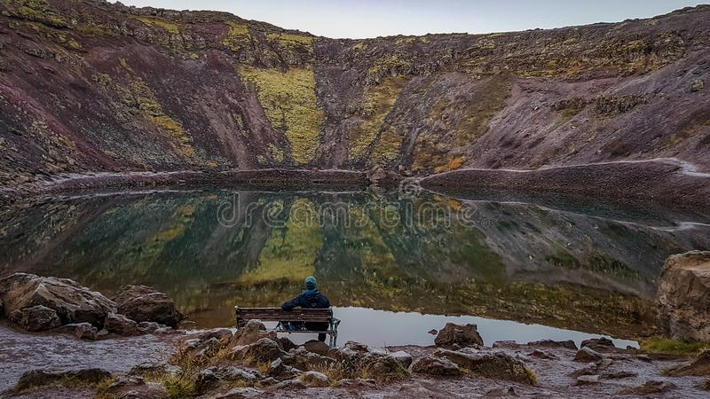 Iceland - Man sitting on a bench in front of a lake stock photo