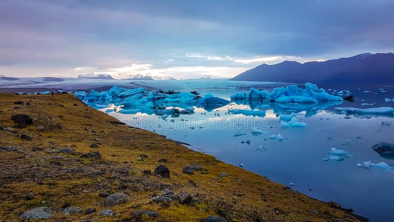 Iceland - Melting glacier. Wast and cold glacier lagoon, with the glacier cap in the back. Huge and massive ice bergs are slowly drifting towards the sea. Global stock photo