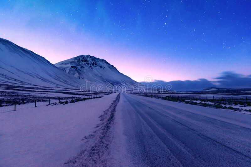 Iceland night landscape. Iceland road trip, the highway along mountains covered with snow, amazing Icelandic landscape, picturesque wintertime view, the night stock photo
