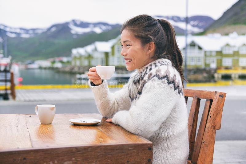 Iceland travel holiday happy Asian girl drinking coffee outside at restaurant wearing icelandic traditional wool sweater. Summer stock photography