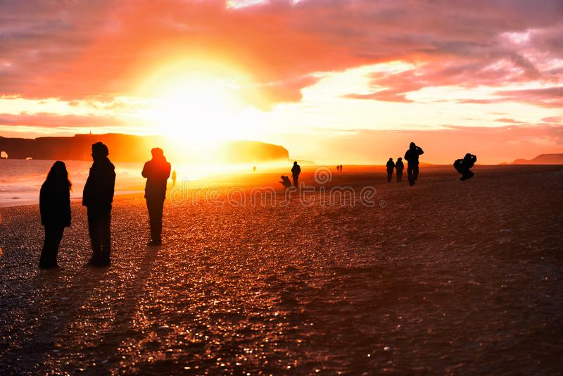 Iceland travel tourists walking on reynisfjara Black Sand Beach. Landscape photography tourists taking pictures, silhouettes of royalty free stock photos