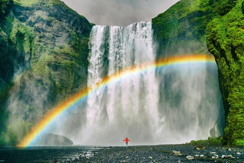 Iceland waterfall travel nature famous tourist destination. Skogafoss waterfall with rainbow and woman under water fall in magical. Landscape popular Europe royalty free stock images