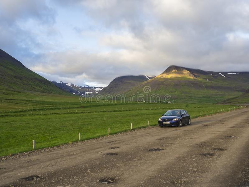 Iceland, west fjords, 30 June, 2018: small black car driving on dirty road through valley in rural northern landscape. With green grass and volcanic hills, and stock photo