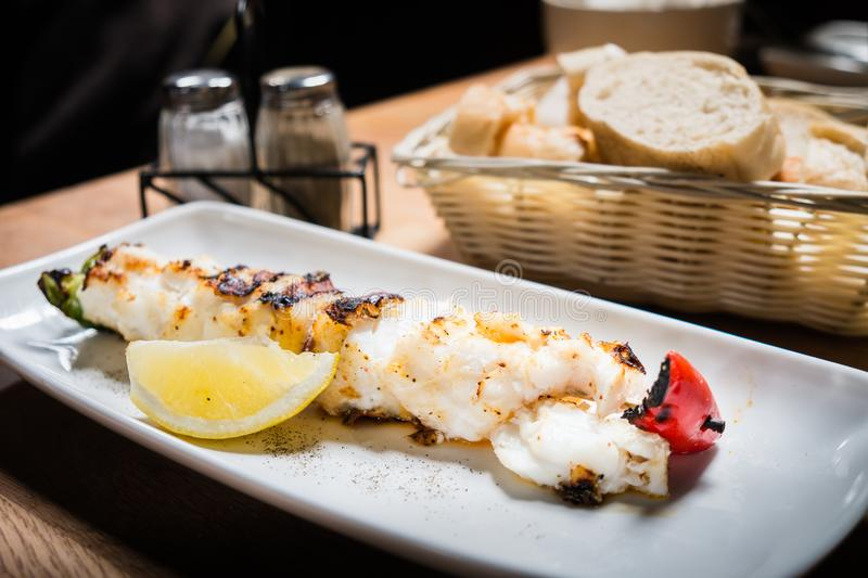 Grilled or roasted icelandic cod fish with lemon on white dish o royalty free stock photos