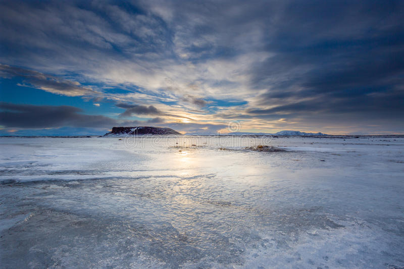 An Icelandic plane of ice covered by a dramatic sundown with reflections. Scenery in Iceland, showing a large plain of ice, mountains in the distance, the sun stock images