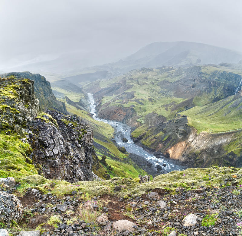 Icelandic stream. Small icelandic stream in a foggy day. View from the top of a rocky mountain royalty free stock photos